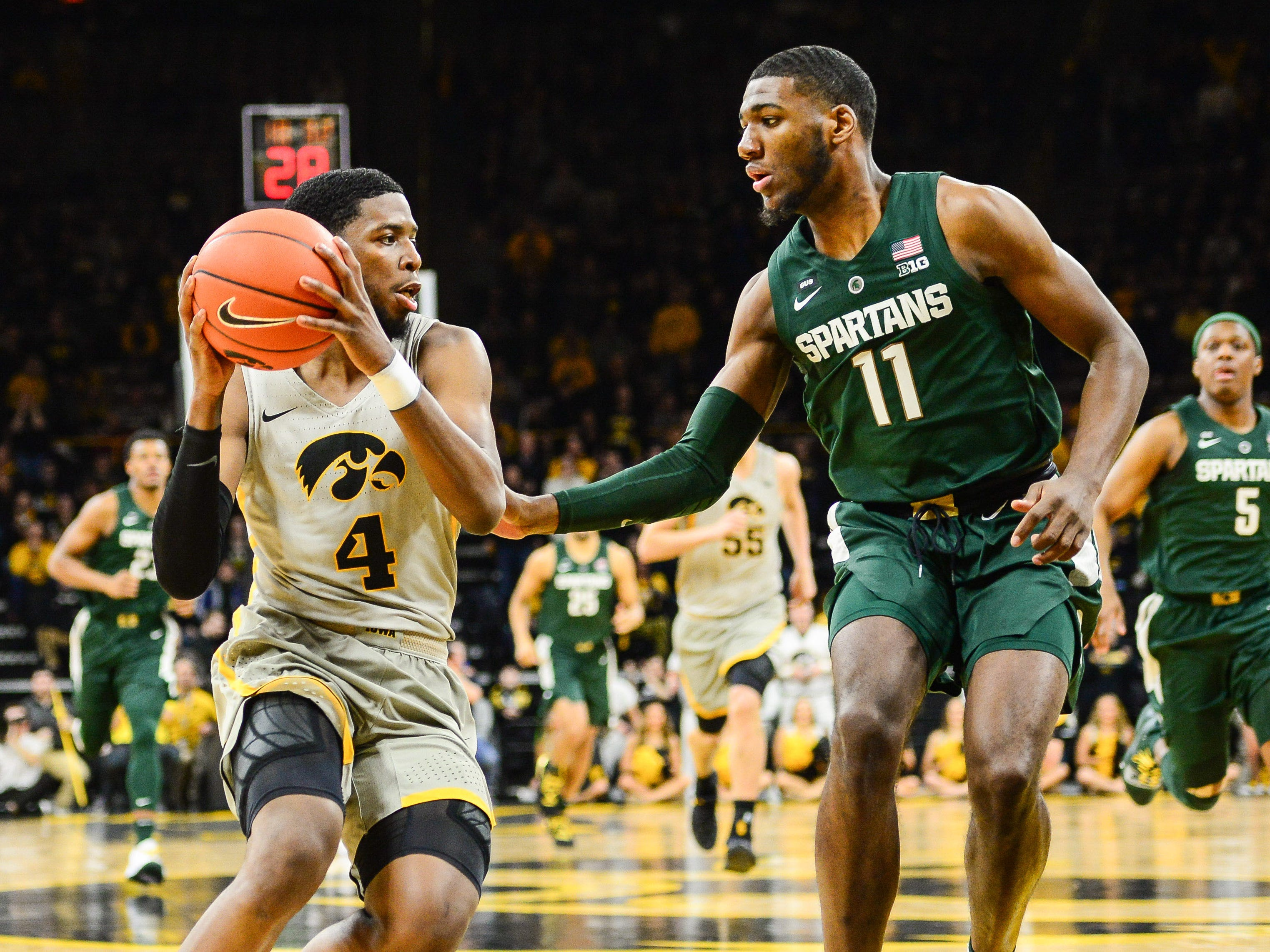 Iowa Hawkeyes guard Isaiah Moss (4) controls the ball as Michigan State Spartans forward Aaron Henry (11) defends during the first half at Carver-Hawkeye Arena.