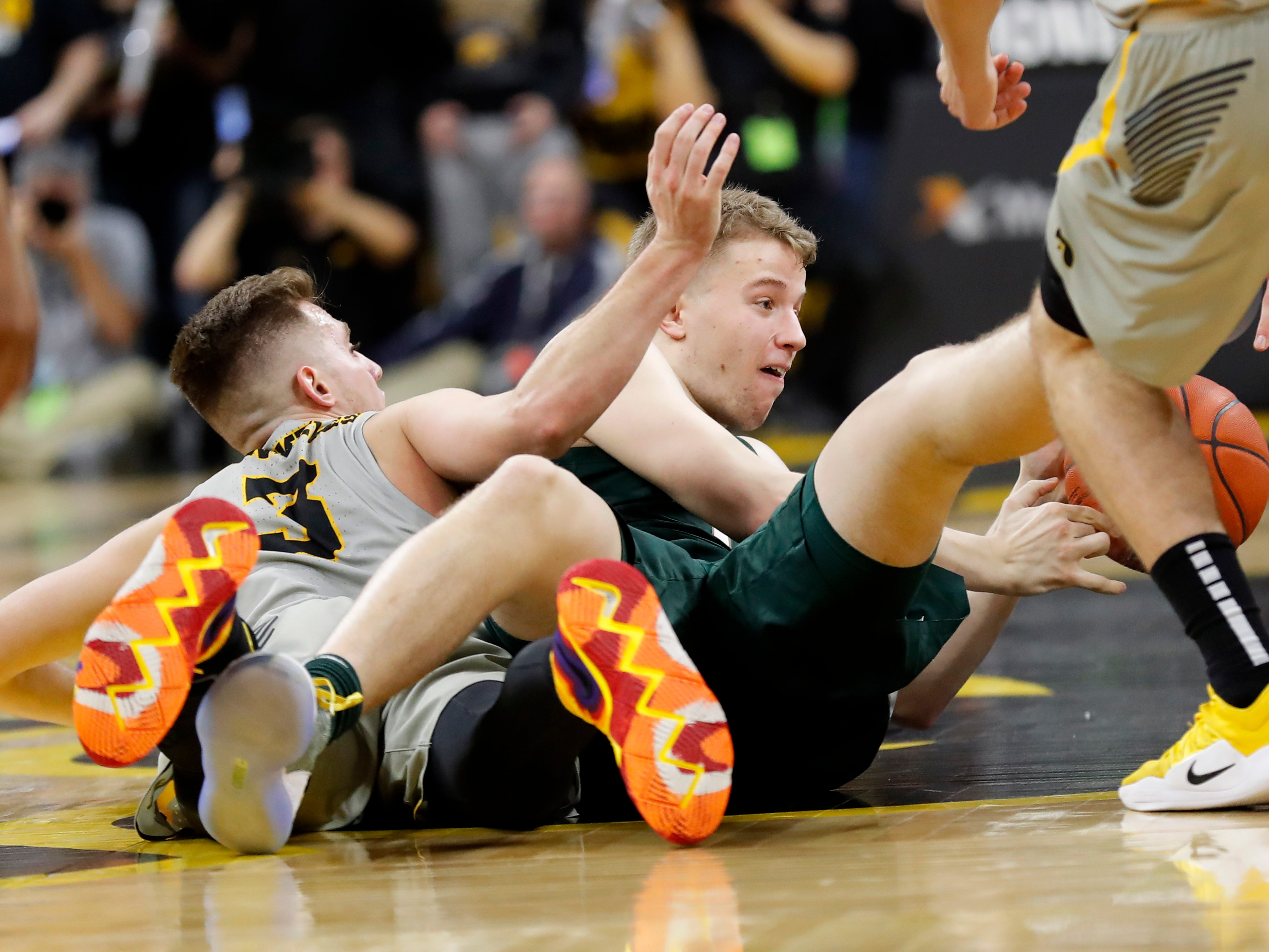 Michigan State forward Thomas Kithier fights for a loose ball with Iowa guard Jordan Bohannon, left, during the first half of an NCAA college basketball game Thursday, Jan. 24, 2019, in Iowa City, Iowa.
