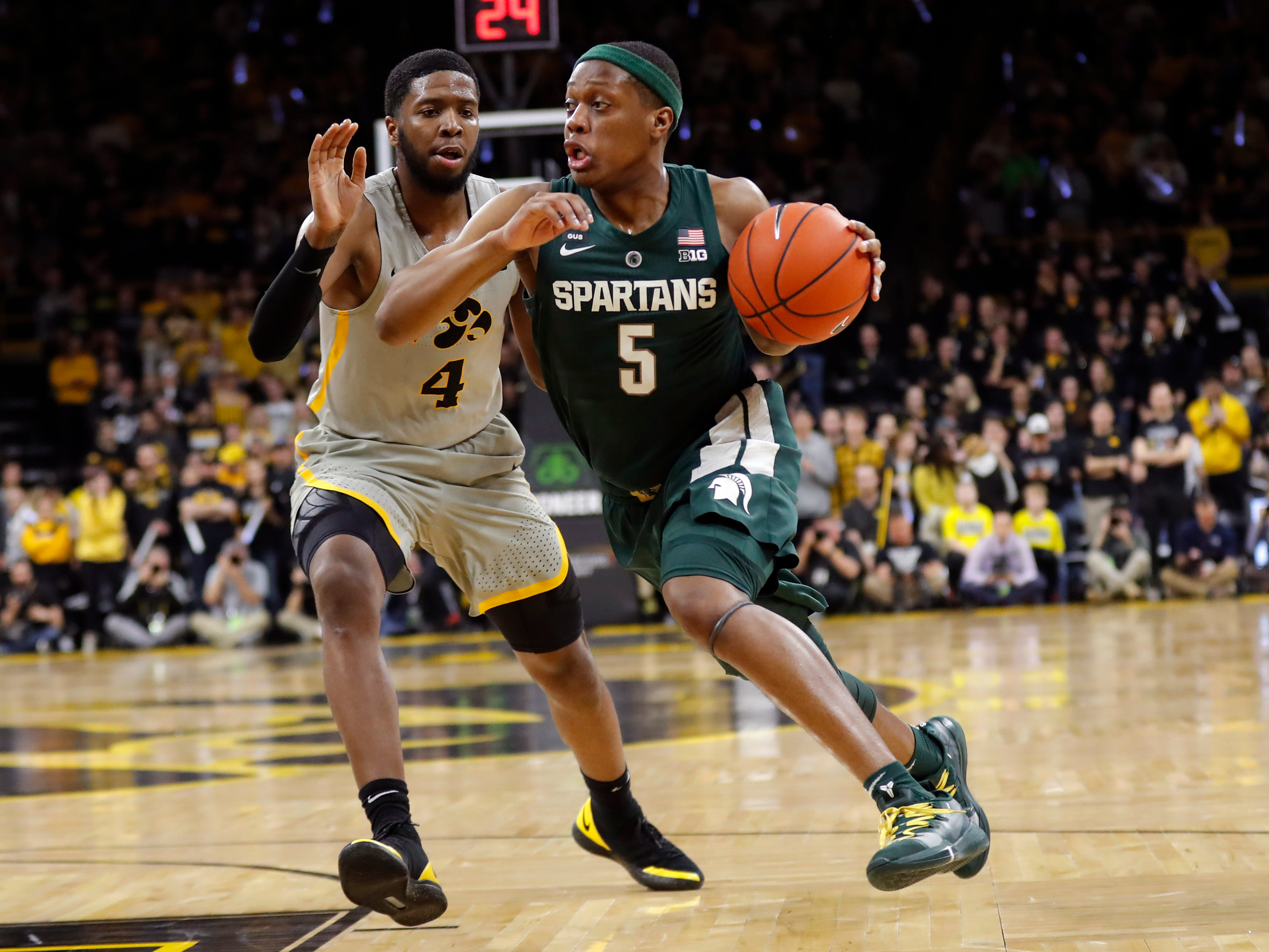Michigan State guard Cassius Winston (5) drives past Iowa guard Isaiah Moss (4) during the first half of an NCAA college basketball game Thursday, Jan. 24, 2019, in Iowa City, Iowa.