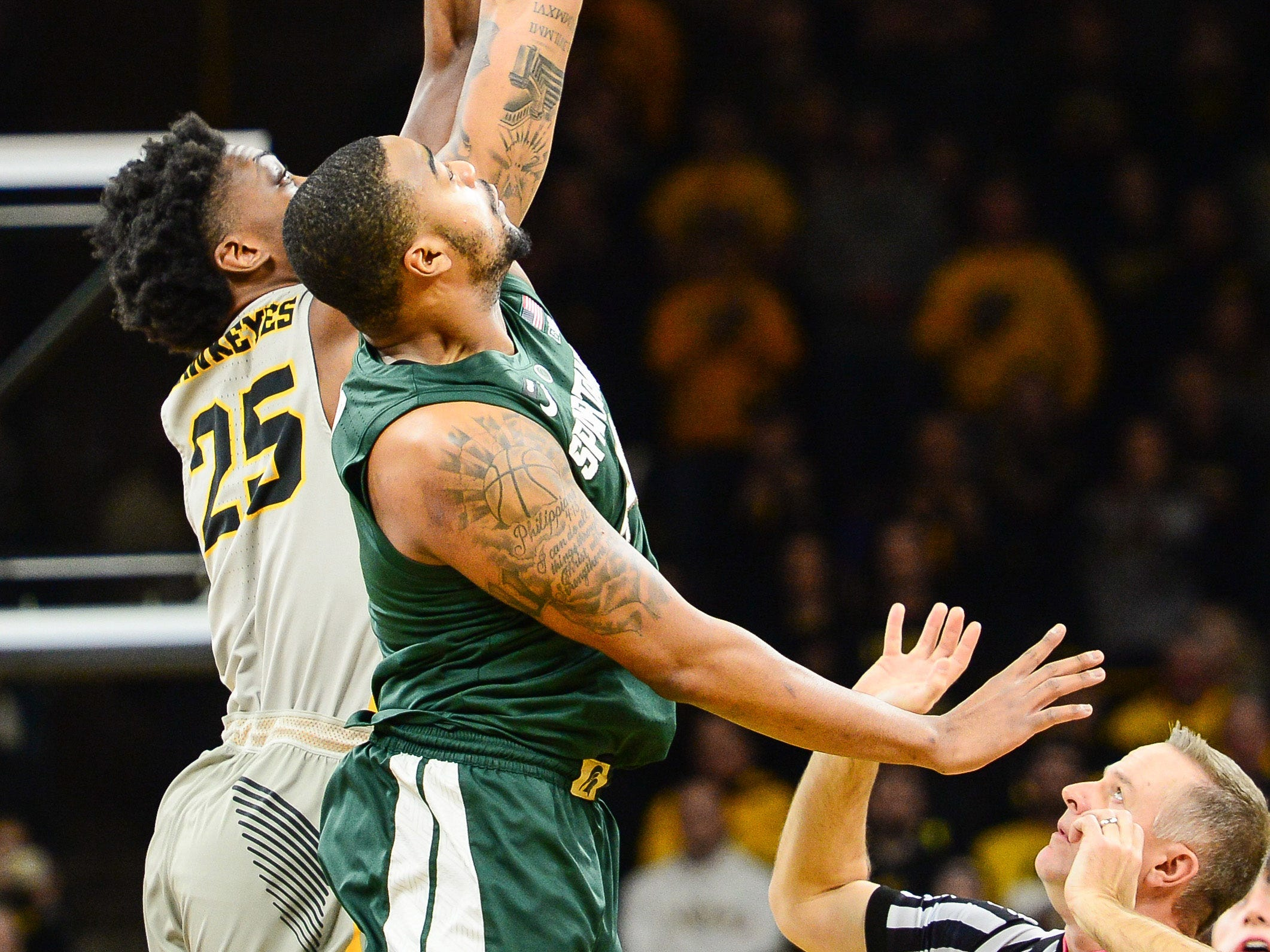 Iowa Hawkeyes forward Tyler Cook (25) and Michigan State Spartans forward Nick Ward (44) battle for the opening tipoff during the first half at Carver-Hawkeye Arena.
