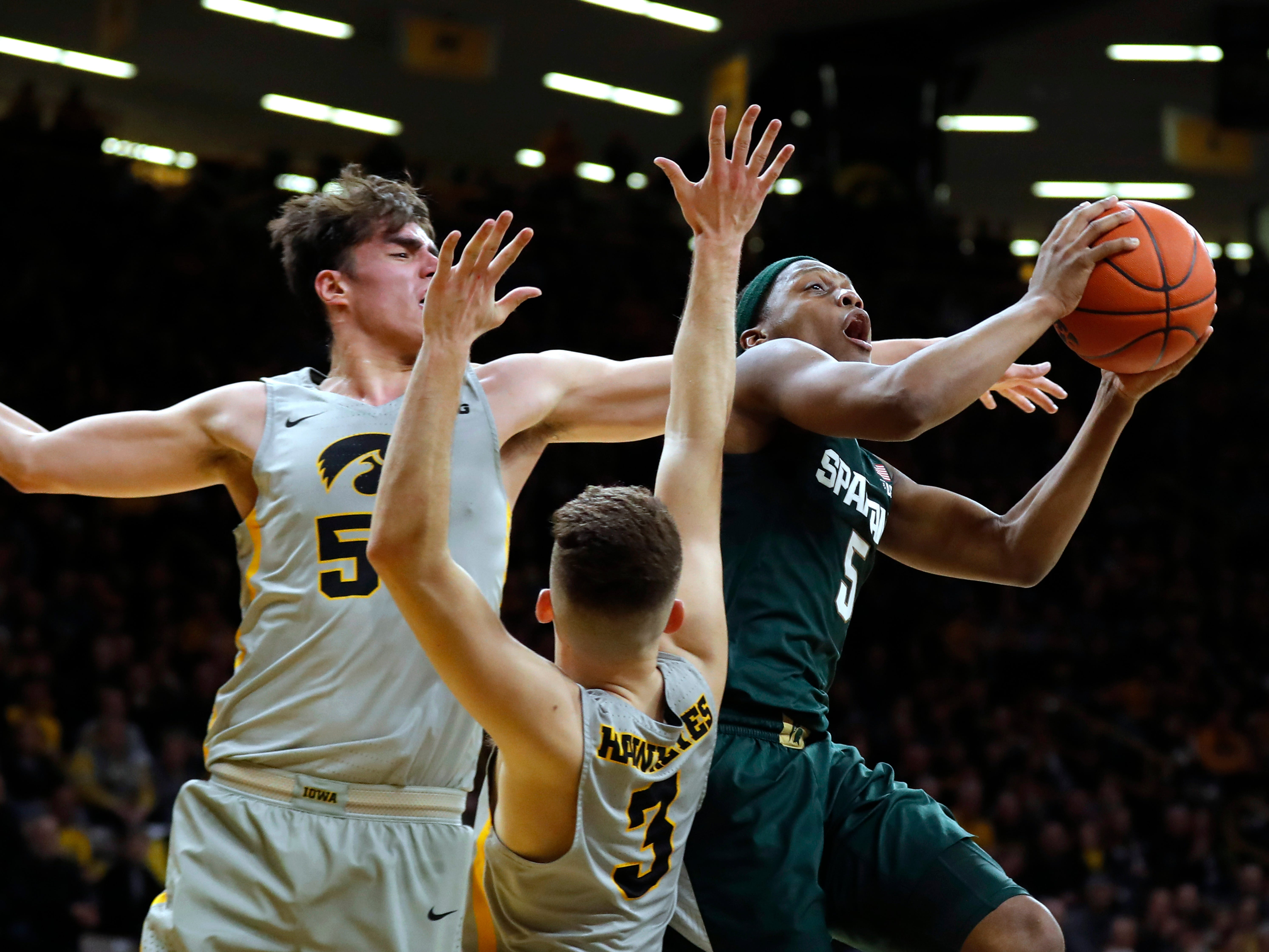Michigan State guard Cassius Winston, right, drives to the basket over Iowa's Luka Garza, left, and Jordan Bohannon (3) during the first half of an NCAA college basketball game Thursday, Jan. 24, 2019, in Iowa City, Iowa.