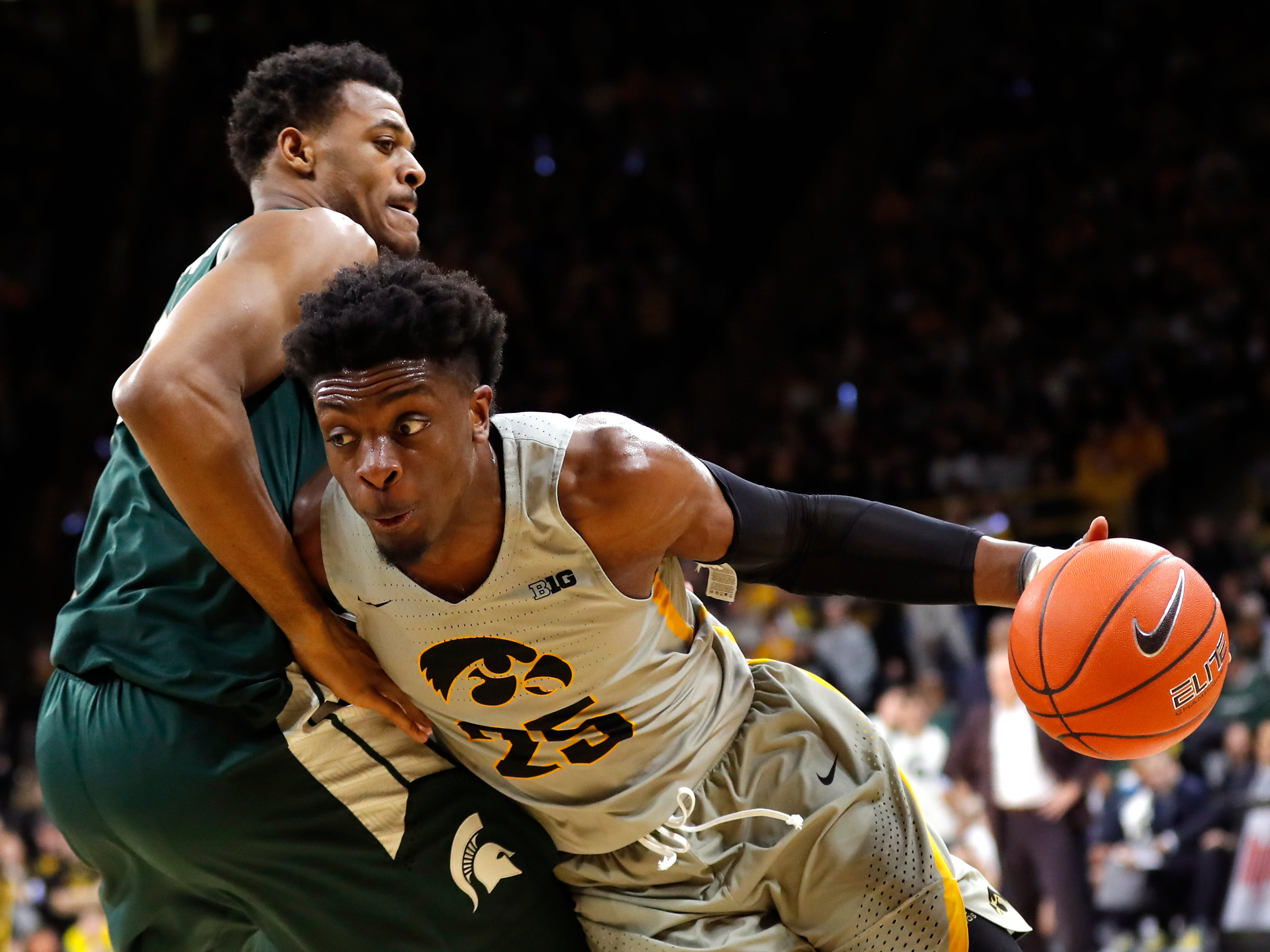Iowa forward Tyler Cook drives past Michigan State forward Xavier Tillman, left, during the second half of an NCAA college basketball game Thursday, Jan. 24, 2019, in Iowa City, Iowa.
