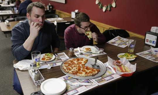 Former employees Paul and Michael Ferracane eat pizza on Saturday, December 29, 2018, at Scotty's Pizza in Marshfield, Wis.