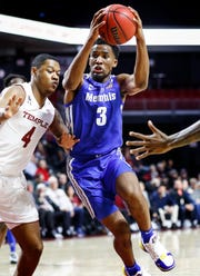Memphis guard Jeremiah Martin (right) drives to the basket by Temple defender J.P. Moorman II (left) during action in Philadelphia, Thursday, January 24, 2019.