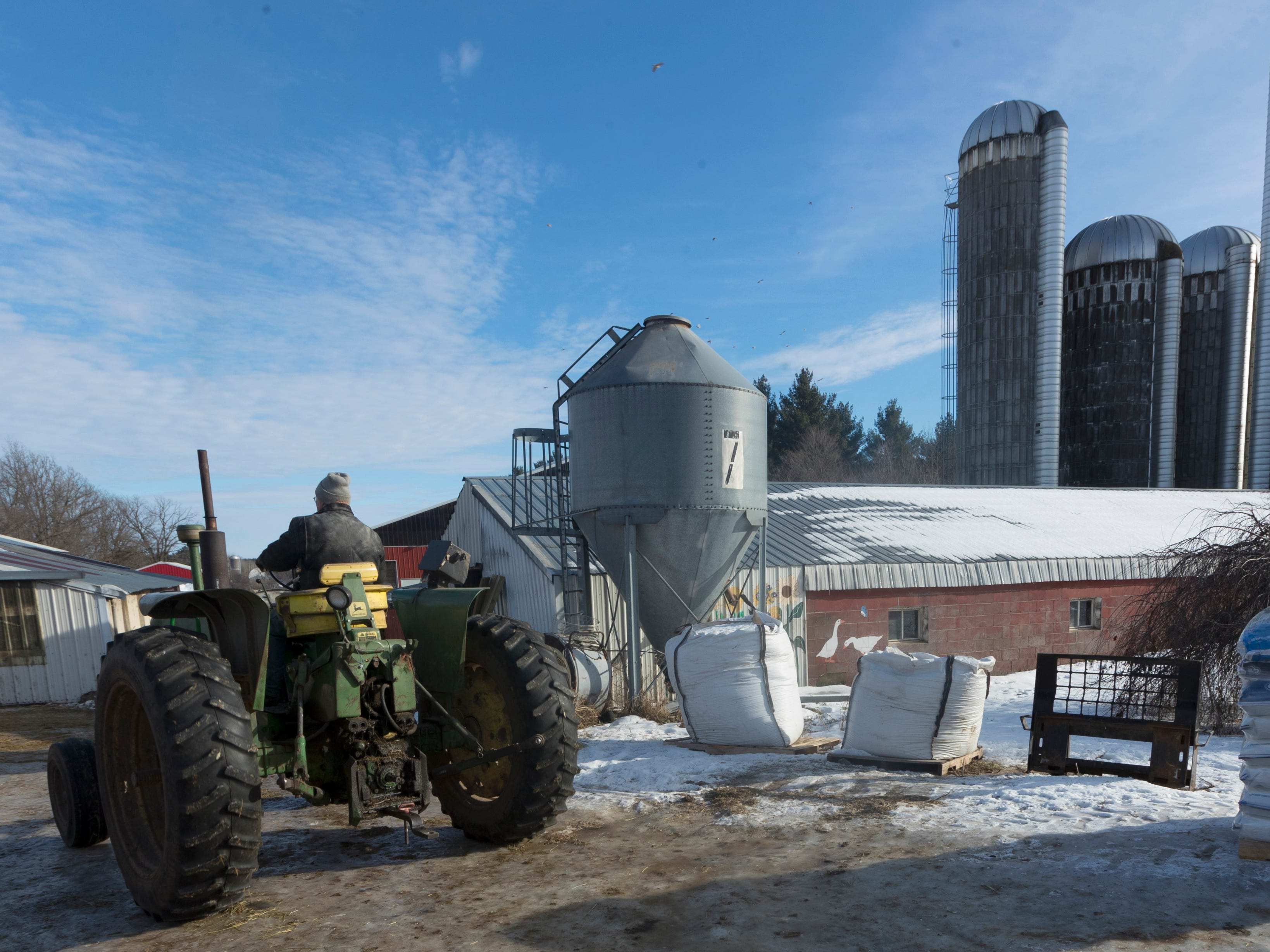Chuck Spaulding moves his 1964 John Deere tractor into a shed while doing chores.