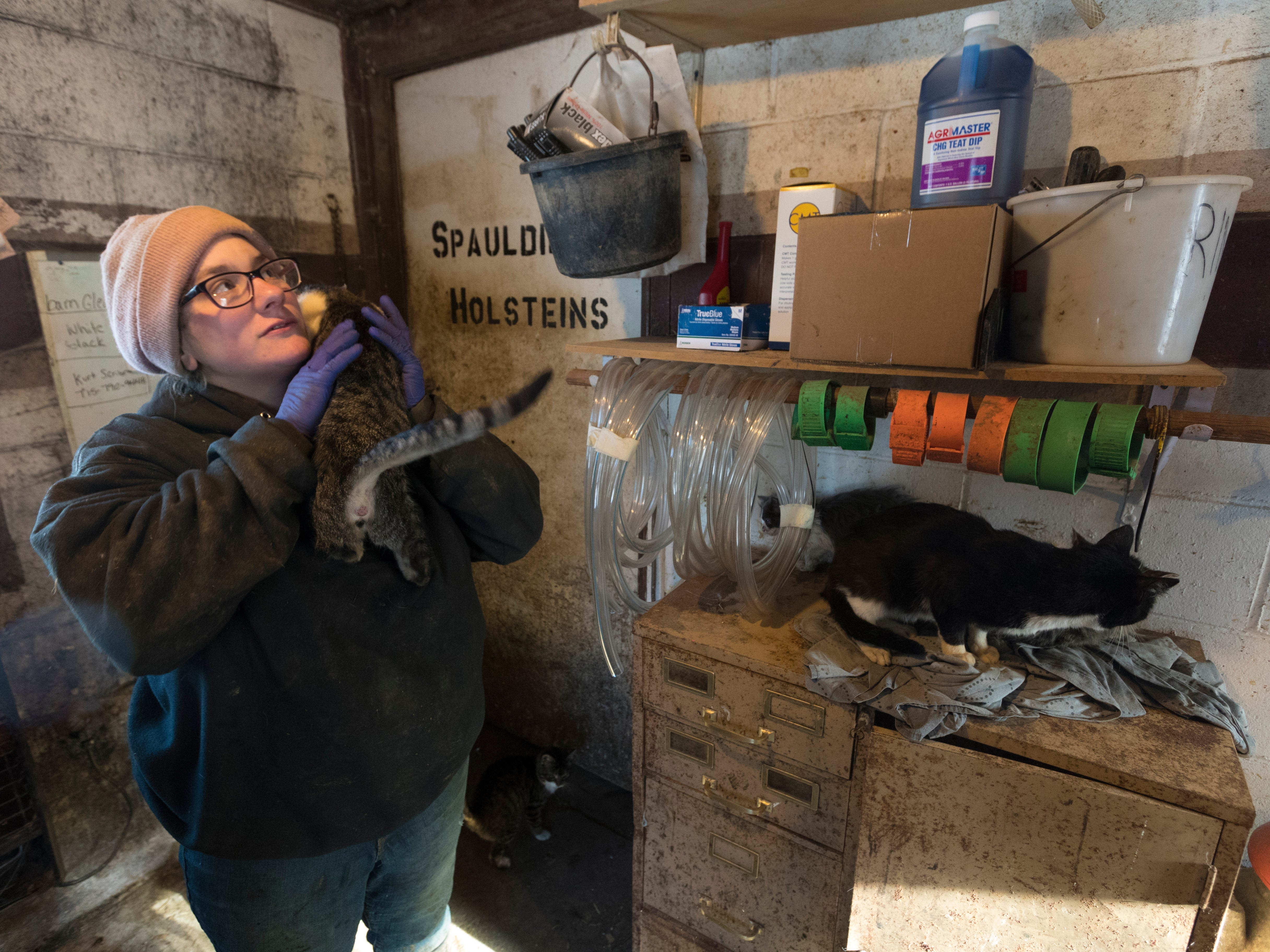 Christy Spexet holds one of the many barn cats. Spexet names every cow and cat on the Spaulding family's farm.