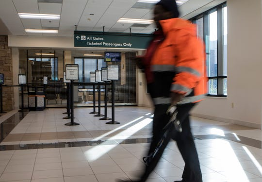 An employee with the Monroe Regional Airport walks past the closed passenger gate where Travel Security Administration employees screen passengers in Monroe, La. on Jan. 25. One flight was cancelled and two others were delayed in the early morning when local TSA agents did not show as the federal shutdown entered day 35.
