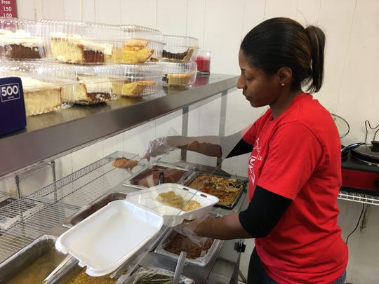 Teheiria Gaines, manager of Breaking Bread, prepares a plate of food. Federal workers who are furloughed can buy a plate of food and get one free.
