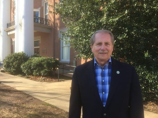 Rutherford County Mayor Bill Ketron posed on historic County Courthouse grounds. The mayor is leading efforts to improve the Civil War-era courthouse. Projects will include removing holly trees behind him that are growing into the building.