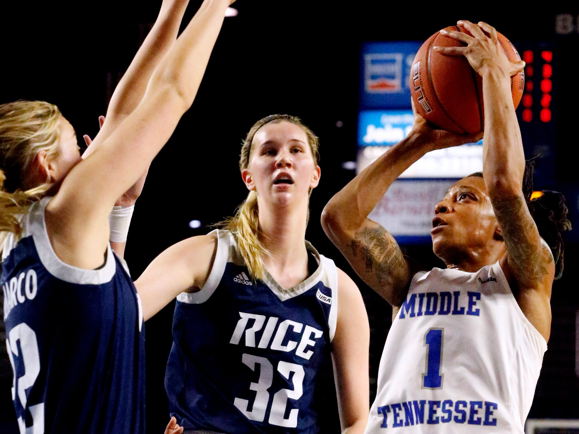 MTSU's guard A'Queen Hayes (1) goes u for a shot as Rice's guard/forward Nicole Iademarco (22) guards her and Rice's center Nancy Mulkey (32) looks on Thursday Jan. 24, 2019.