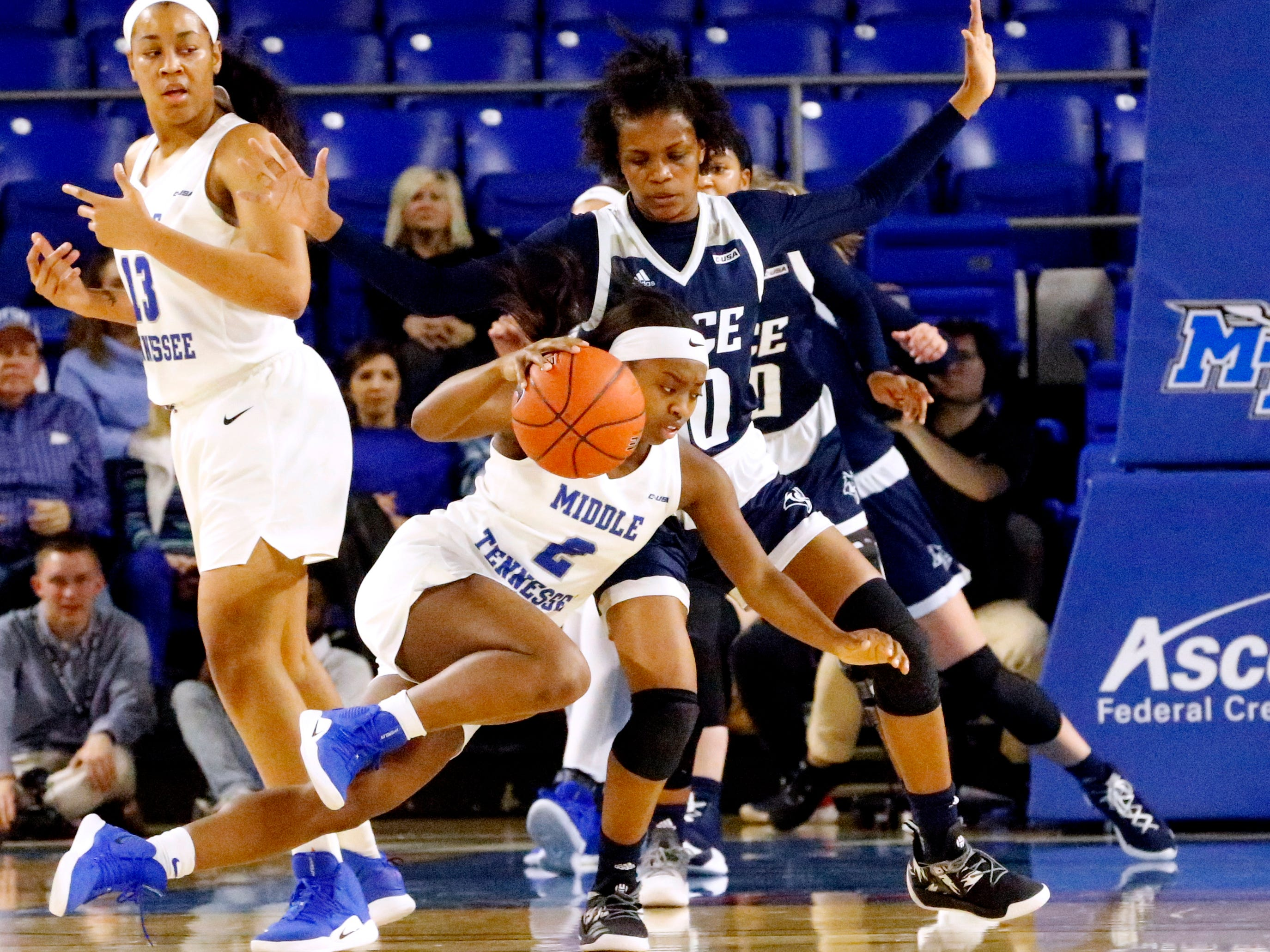 MTSU's guard Taylor Sutton (2) falls to the ground with the ball as Rice's guard Jasmine Smith (10) guards her on Thursday Jan. 24, 2019.