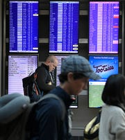 People walk by video screens showing arriving and departing flights  at Nashville International Airport on Friday, Jan. 25, 2019.