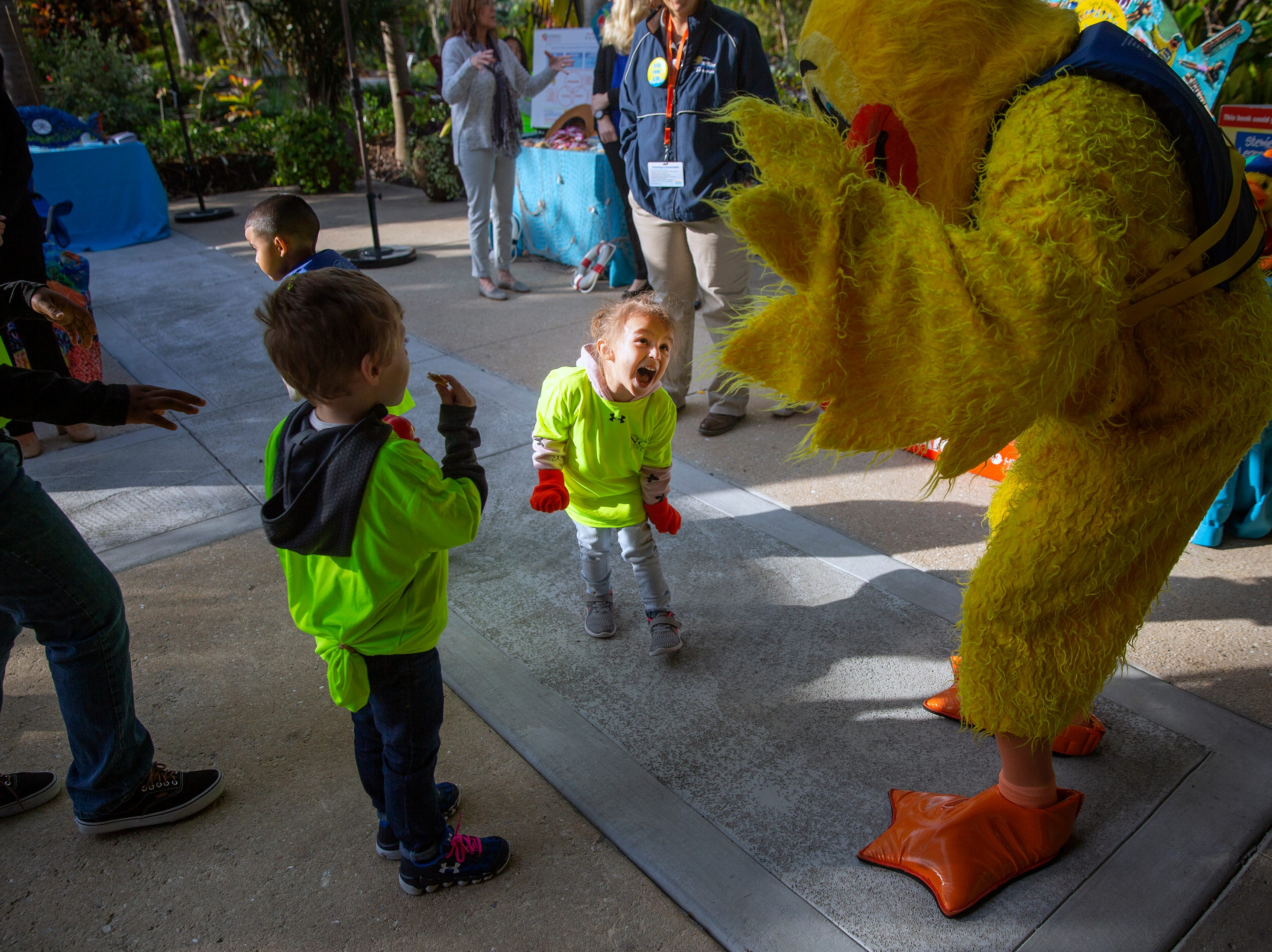 Sawyer Bewley-Rojas, center, plays with Stewie the Duck, the mascot for Safe and Healthy Children's Coalition of Collier County, during the Naples Winter Wine Festival Meet the Kids Day, Friday, Jan. 25, 2019, at Naples Botanical Garden.