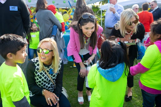 Lauren Brady, from left, Jessica Brady and Patty Brady talk with Axel Alvarez Zuniga, 6, from left, Jennifer Thomas Rosario, 6, and Sherly Temaj Mazariegos, 7, with the Redland Christian Migrant Association, on Friday, Jan. 25, 2019, during the Naples Winter Wine Festival's Meet the Kids Day at Naples Botanical Garden.