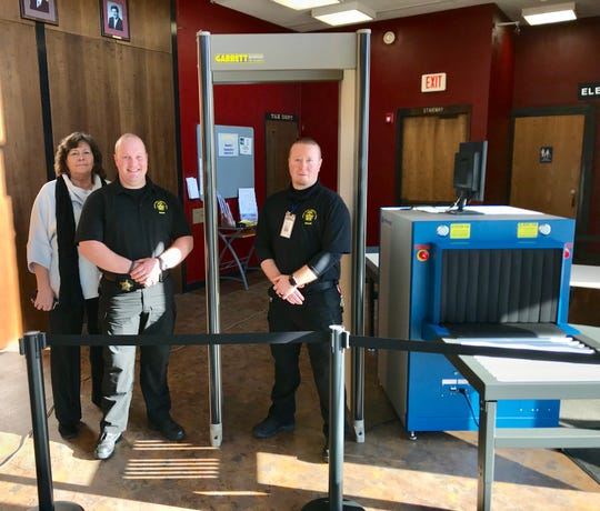 Standing next to new security equipment in the Newark Municipal Building lobby are, from left, Municipal Court Clerk Marcia Phelps, and deputy bailiffs Aaron Minot and Kris White.