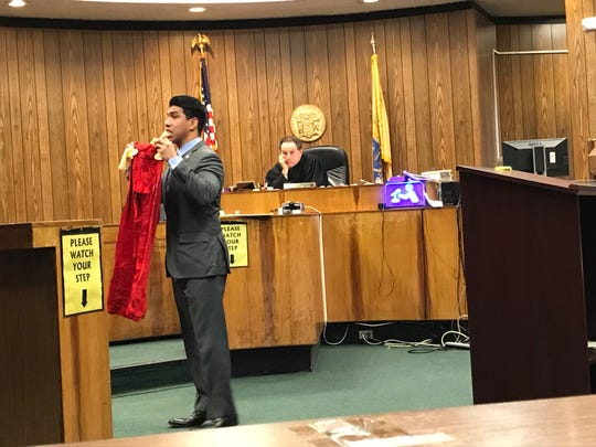 Assistant Prosecutor Jonathan Barrera showing the jury the pants the woman wore on the night of Aug. 16, 2000.