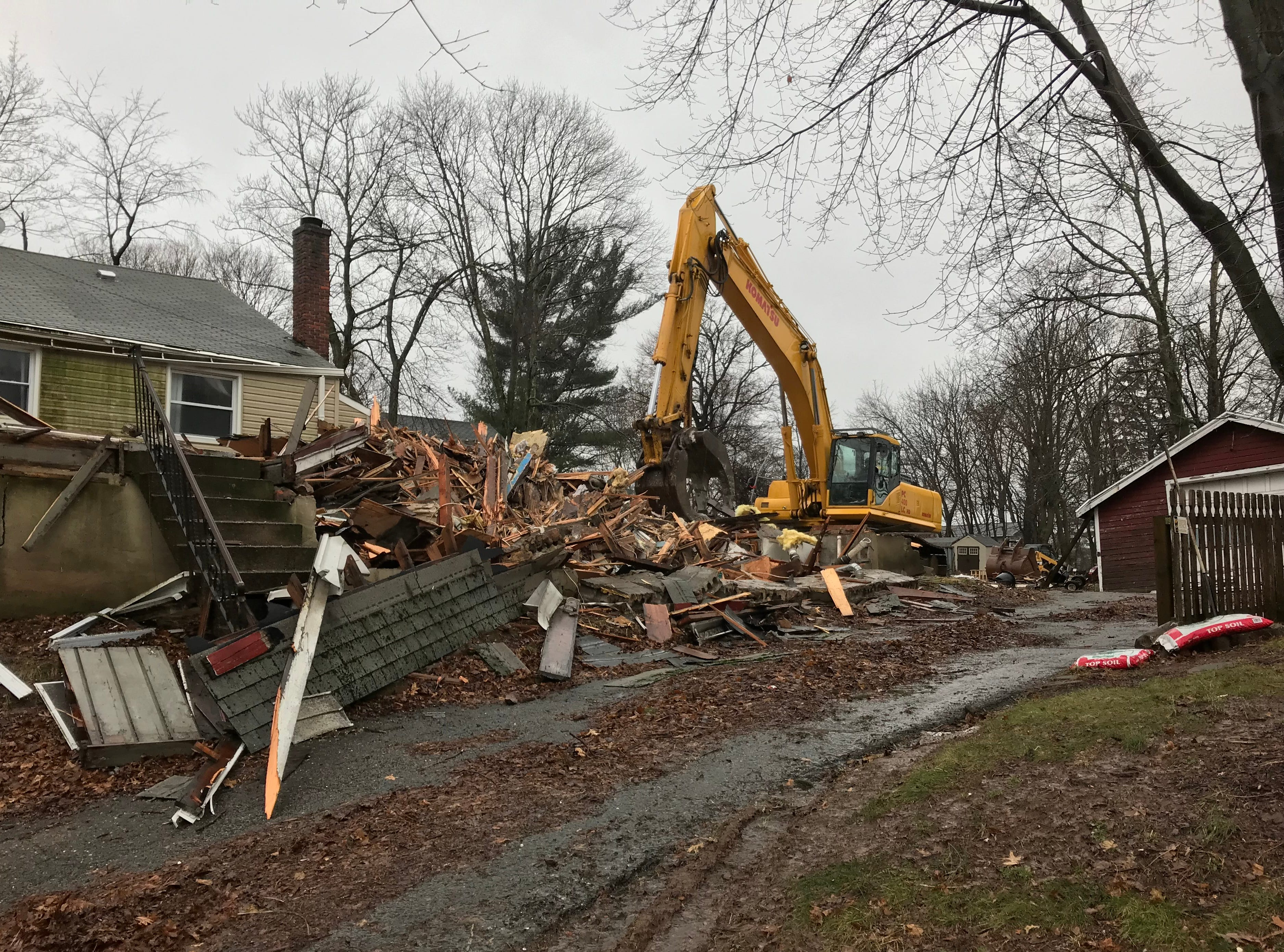 A grapple demolishes a building on South End Firehouse's property in Cedar Grove on Jan. 24, 2019.