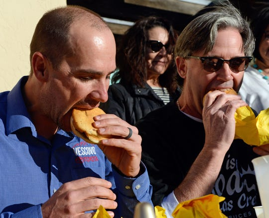 "George Vescovo, president of Vescovo Toyota, left, and Richard Coltharp, publisher of the Las Cruces Bulletin, compete in a hamburger-eating contest at Day's Hamburgers on Wednesday, Jan. 23, as part of the ""Construction Compadres"" program, created by three local chambers of commerce to draw attention to local businesses hurt by road construction projects."