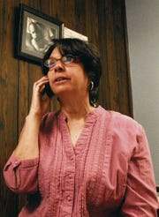In this 2013 file photo, Nancy Harris of Court Appointed Special Advocates takes a phone call in her office.