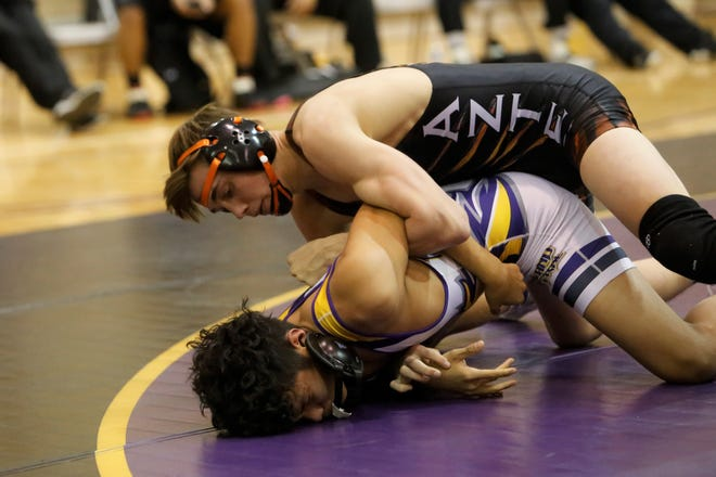 Aztec's Garrett Birzer locks up the left arm of Kirtland Central's Tobey John in the 138-pound division match during Thursday's District 1-4A wrestling opener at KCHS. Visit daily-times.com to see the latest sports photo galleries and video highlights.