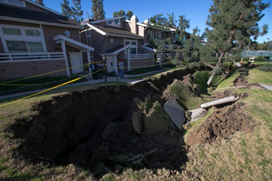 A sinkhole is seen in a condominium complex Thursday, Jan. 24, 2019, in La Habra, Calif.  The ground collapsed in a green space between the residences toppling trees. The hole is estimated to be about 80 feet (24 meters) long and 20 feet (6 meters) wide.