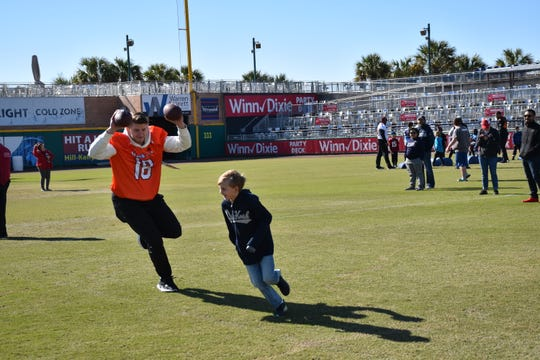 Former LSU star tight end Foster Moreau has some fun with a young participant in Friday's Senior Bowl players' visit to Blue Wahoos Stadium.  Kids from the NFL Flag Pensacola youth football league were able to have a short workout with the future NFL players.