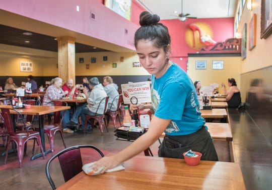 Server Olivia Perry wipes down a table at the Ruby Slipper restaurant in downtown Pensacola on Friday, January 25, 2019.  The Ruby Slipper was one of a handful of local restaurants offering free meals to Federal employees during the government shutdown.