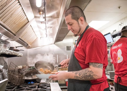 Kitchen manager Frank Sandoval plates an order of shrimp and grits at the Ruby Slipper restaurant in downtown Pensacola on Friday, January 25, 2019.  The Ruby Slipper was one of a handful of local restaurants offering free meals to Federal employees during the government shutdown.