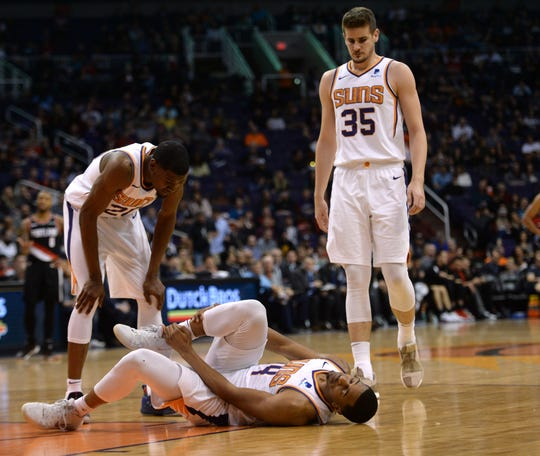 Jan 24, 2019; Phoenix, AZ, USA; Phoenix Suns forward Josh Jackson (20) and Phoenix Suns forward Dragan Bender (35) look on as Phoenix Suns forward Phoenix Suns guard De'Anthony Melton (14) grabs his injured leg during the second half of the game against the Portland Trail Blazers at Talking Stick Resort Arena. Mandatory Credit: Joe Camporeale-USA TODAY Sports