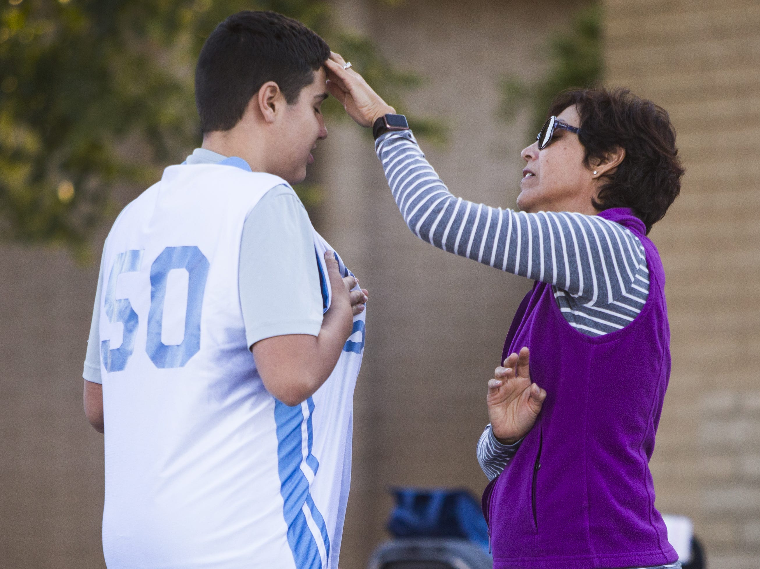 Luke Stockstad, who has autism, gets his hair brushed by his mom, Lisa Stockstad, before going in for his team, St. Mary-Basha Catholic School, as they play St. John Bosco, Tuesday, November 27, 2018.