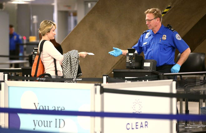 A Transportation Security Administration agent works a checkpoint on Jan. 23 at Phoenix Sky Harbor Airport Terminal 4. TSA agents are working without pay during the government shutdown.