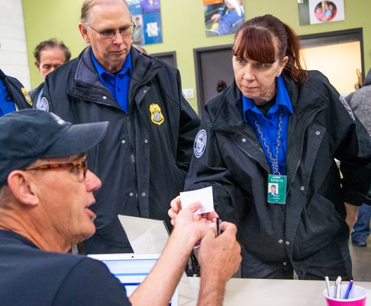TSA agents Steve McKenzie, left, and Gisele Bamber check in at the United Food Bank in Mesa, Friday, January 25, 2019.  Bamber, McKenzie and other federal workers have been living without pay for the past month.  President Trump announced Friday afternoon that an agreement had been reached to end the shutdown for at least the next three weeks.