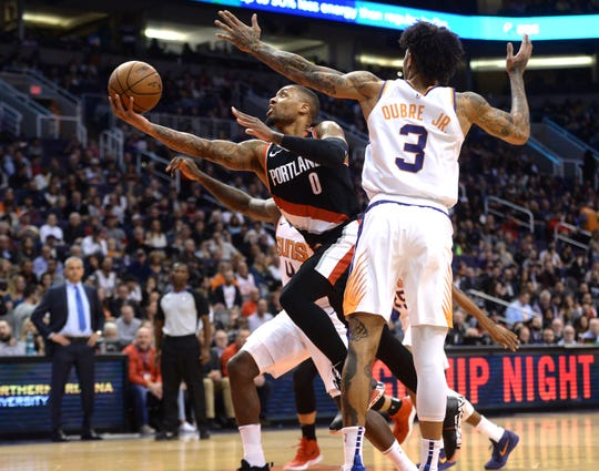 Jan 24, 2019; Phoenix, AZ, USA; Portland Trail Blazers guard Damian Lillard (0) shoots the ball past Phoenix Suns forward Kelly Oubre Jr. (3) during the first half at Talking Stick Resort Arena. Mandatory Credit: Joe Camporeale-USA TODAY Sports