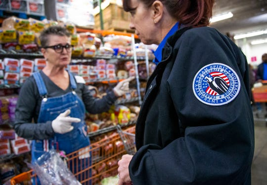 TSA agent Gisele Bamber, right, goes through the United Food Bank in Mesa to get food, Friday, January 25, 2019.  Bamber and other federal workers have been living without pay for the past month.  President Trump announced Friday afternoon that an agreement had been reached to end the shutdown for at least the next three weeks.