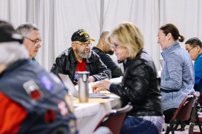 Army veteran Jack Rynes Jr. sits down with a volunteer at the 2019 Veterans StandDown at the Arizona State Fairgrounds in Phoenix, Arizona on  Jan. 25, 2019.