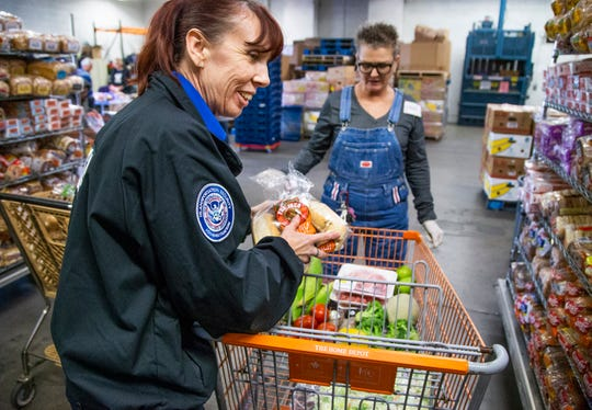 TSA agent Gisele Bamber, left, goes through the United Food Bank in Mesa to get food, Friday, January 25, 2019.  Bamber and other federal workers have been living without pay for the past month.  President Trump announced Friday afternoon that an agreement had been reached to end the shutdown for at least the next three weeks.