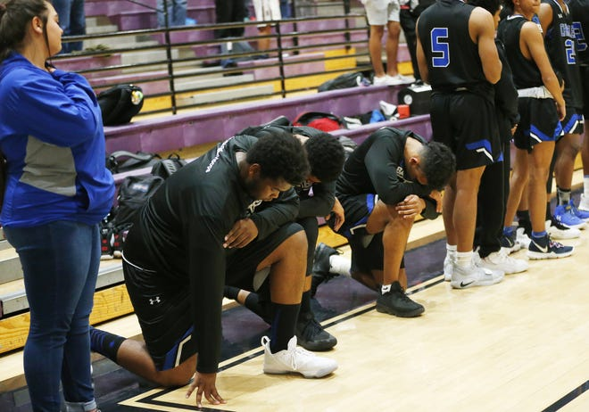 Chandler High basketball player kneel during the national anthem before a game against Hamilton on Jan. 22.