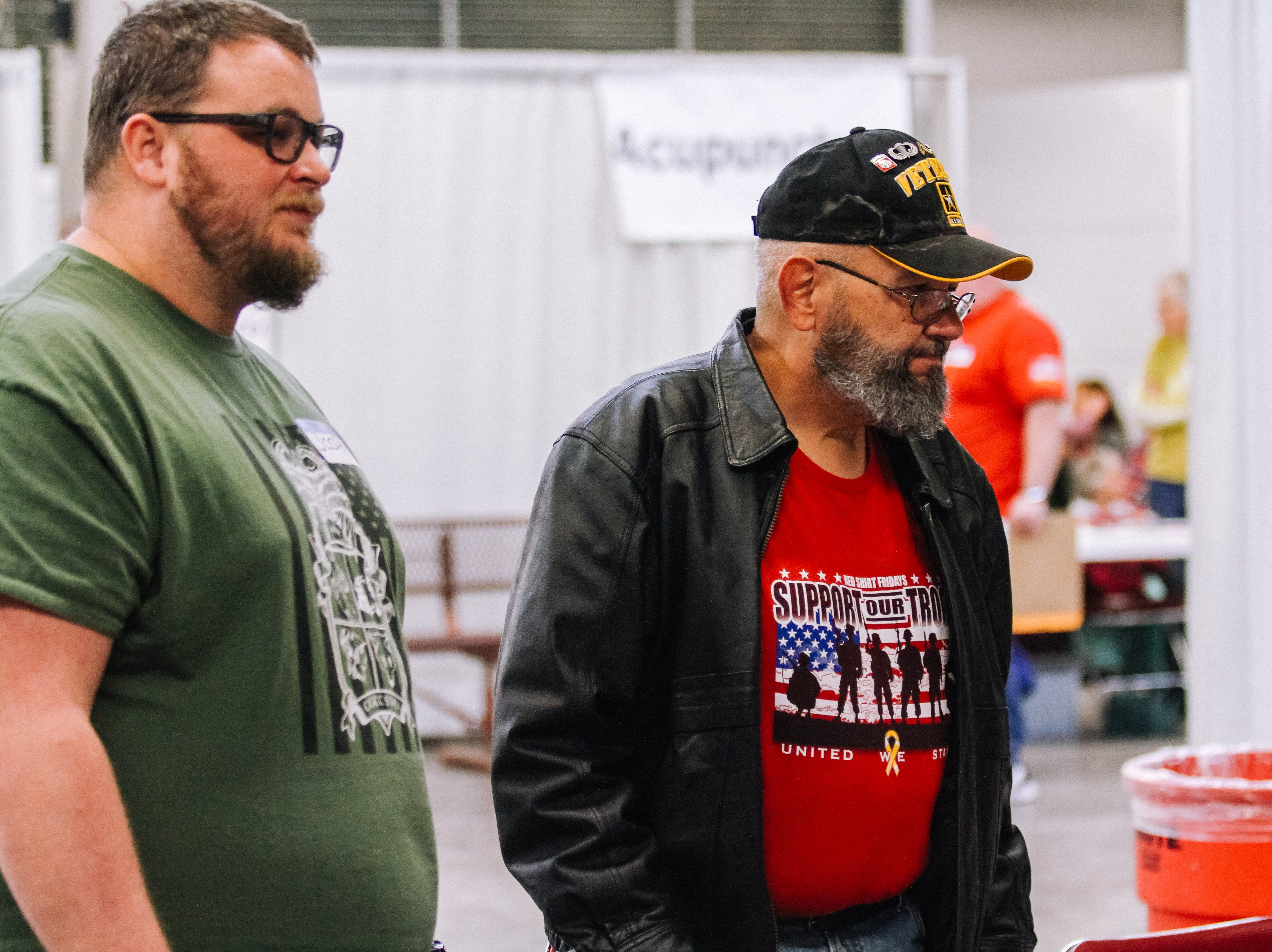 Army weteran Jack Rynes Jr. stands in line to apply for glasses with volunteer Josh Downing at the 2019 Veterans StandDown at the Arizona State Fairgrounds in Phoenix on Jan. 25, 2019.