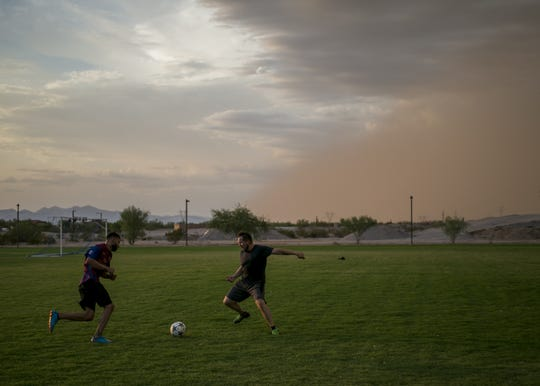 Cristian Martinez and Rosendo Gonzalez, left, play soccer as a dust storm approaches near Estrella Foothills High School on Aug. 12.