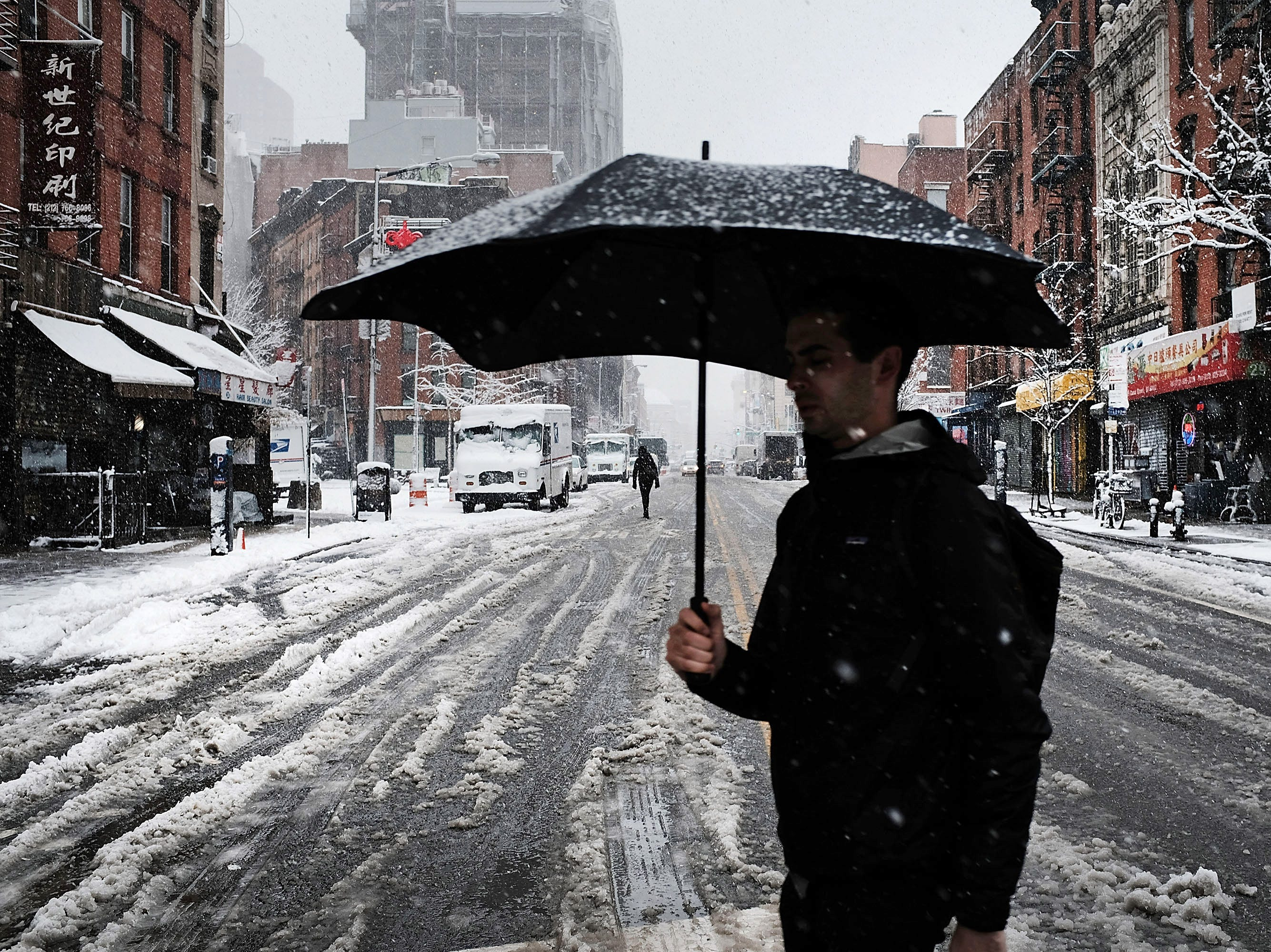 NEW YORK, NY - APRIL 02:  A pedestrian walks in the morning snow during an early spring storm on April 2, 2018 in New York City. New York City and much of New England has experienced a winter season with significant snow fall and a large number of storms that disrupted life for residents throughout the region.  (Photo by Spencer Platt/Getty Images)