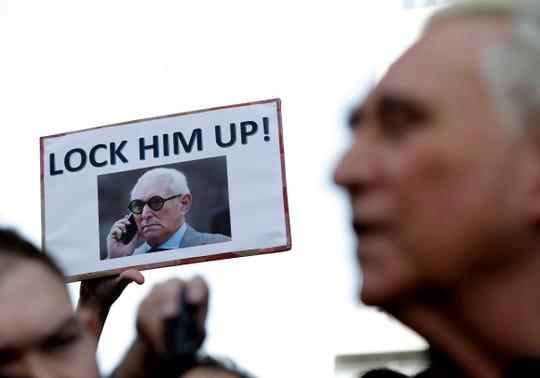 Un manifestante muestra un cartel con contra de Roger Stone, colaborador de Trump que fue arrestado y luego puesto en libertad bajo fianza.