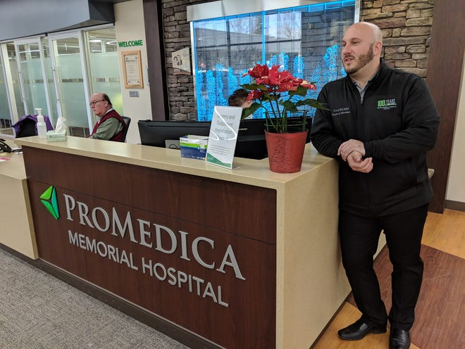Corey Leber, ProMedica Memorial Hospital's director of operations, greets guests as they enter the hospital's renovated front entrance.