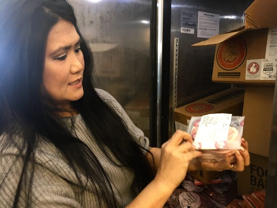 Carmela Burns of SOS Food Pantry shows a package of meat available at the pantry on Friday, Jan. 25, 2019. SOS had been assisting federal workers affected by the shutdown.
