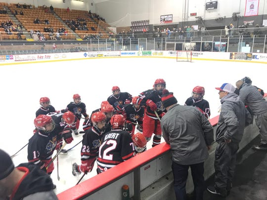 The Port Huron Flags PeeWee AA team talks during its first intermission Friday at McMorran Arena.