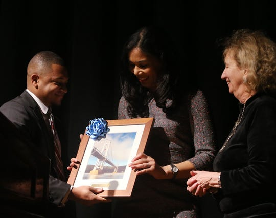 Keynote speaker Kimbriell Kelly receives a framed print of the Mid-Hudson Bridge from Catharine Street Community Center's, from left, Freddimir Garcia and Betsy Kopstein Stuts during the Martin Luther King Jr. Breakfast in the City of Poughkeepsie on January 25, 2019.