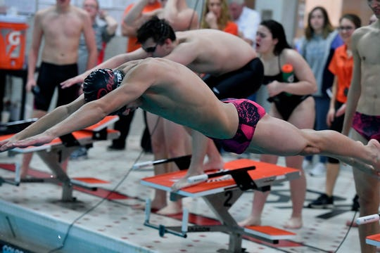 Dover anchor Tanner Gladfelter leaps off the starting block as Devon Lonergan of York Suburban waits for his turn, Thursday, January 24, 2019.John A. Pavoncello photo