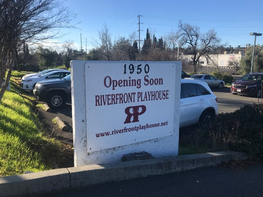 A sign announcing Riverfront Playhouse's new downtown theater.