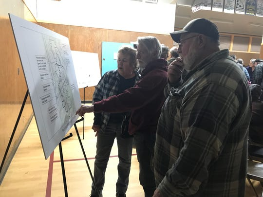 Intermountain residents Carol Forster, left, and Rich Forster, center, look at a locater map of the Fountain Wind project at Thursday's public meeting in Montgomery Creek.
