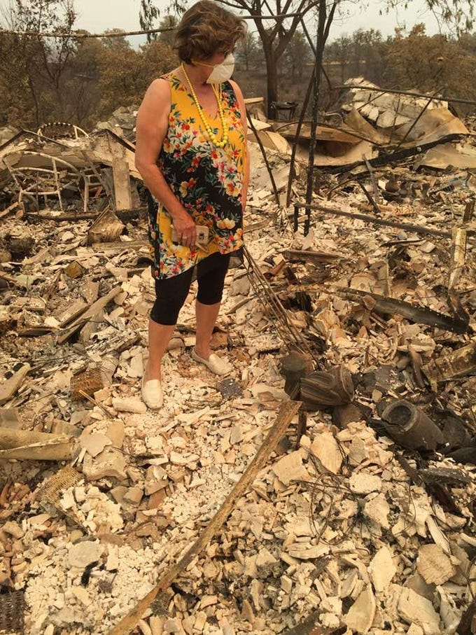 Parvin Carter sifting through the rubble of her home after the Carr Fire.