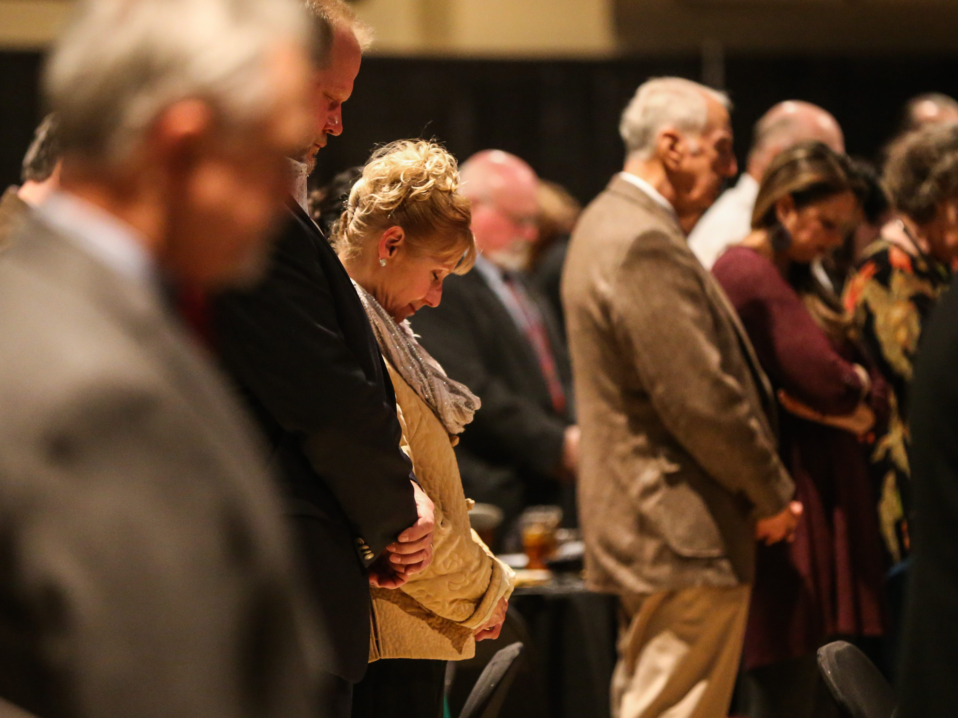 People pray at the start of the San Angelo Chamber of Commerce Annual Banquet Thursday, Jan. 24, 2019, at McNease Convention Center.
